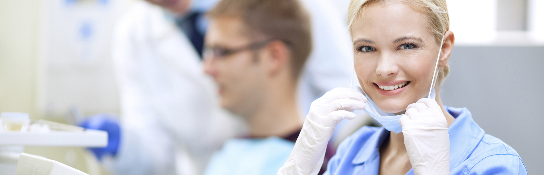 Portrait of a smiling female dentist looking at camera,in background patient having dental treatment