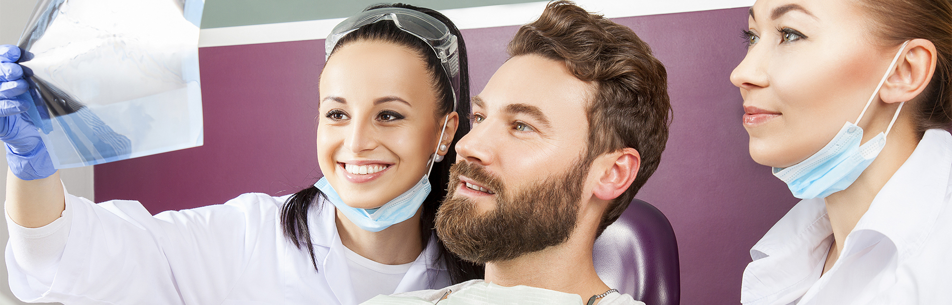 Smiling female doctor and her assistant showing teeth x-ray to male patient in dental hospital. Handsome male patient sitting in chair smilling with straight white teeth and looking at dental x-ray.